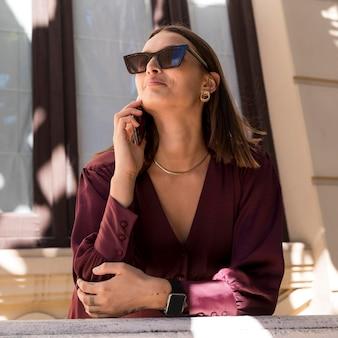 Middellange geschoten smileyvrouw die op telefoon spreekt