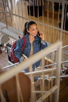 Middellange geschoten student die aan de telefoon praat