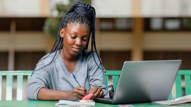 Middellange geschoten student die met laptop studeert