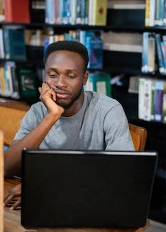 Middellange geschoten student met laptop