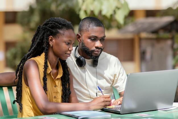 Middellange geschoten studenten die met laptop werken