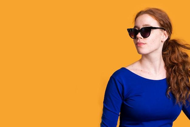 Middellange geschoten trendy vrouw met zonnebril en exemplaar-ruimte