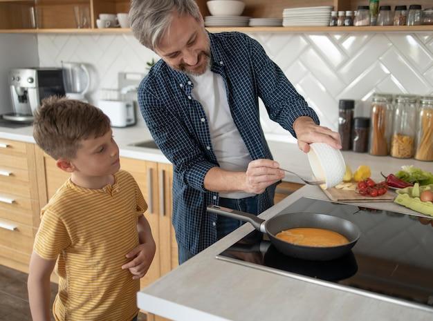 Middellange geschoten vader die omelet kookt
