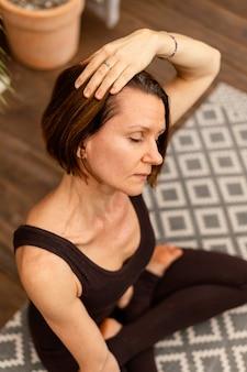 Middellange geschoten vrouw die binnen mediteert