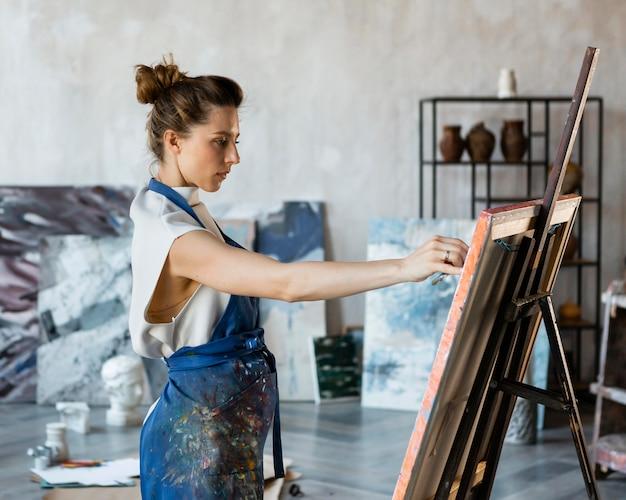 Middellange geschoten vrouw die binnenshuis schildert