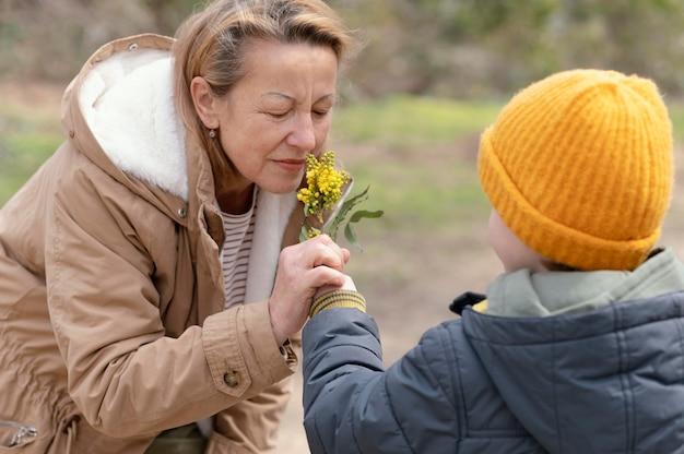 Middellange geschoten vrouw die bloemen ruikt