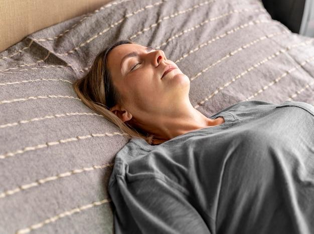 Middellange geschoten vrouw die in bed legt