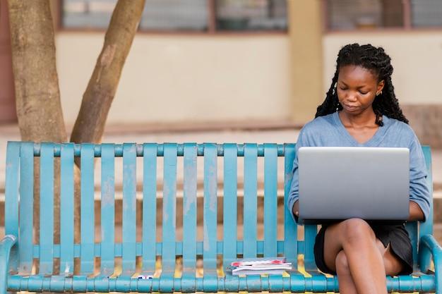 Middellange geschoten vrouw die met laptop studeert