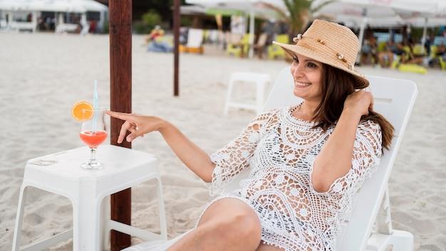 Middellange geschoten vrouw die op zonnebank legt