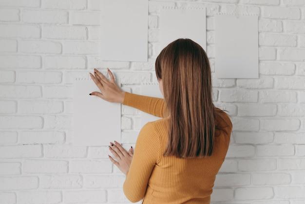 Middellange geschoten vrouw die papier op de muur zet