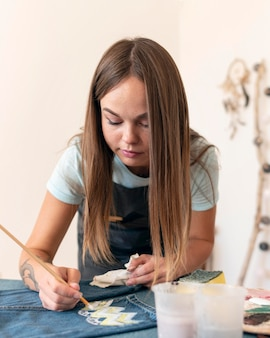 Middellange geschoten vrouw die spijkerbroek schildert