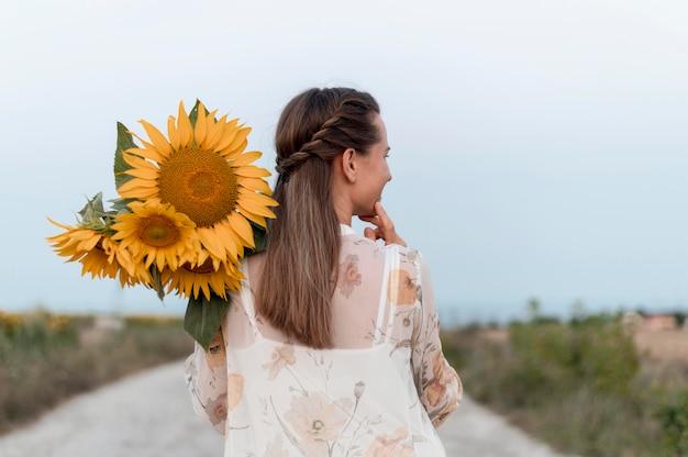 Middellange geschoten vrouw met bloemen
