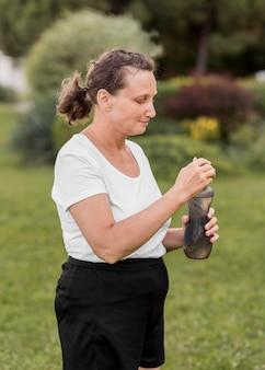 Middellange geschoten vrouw met waterfles