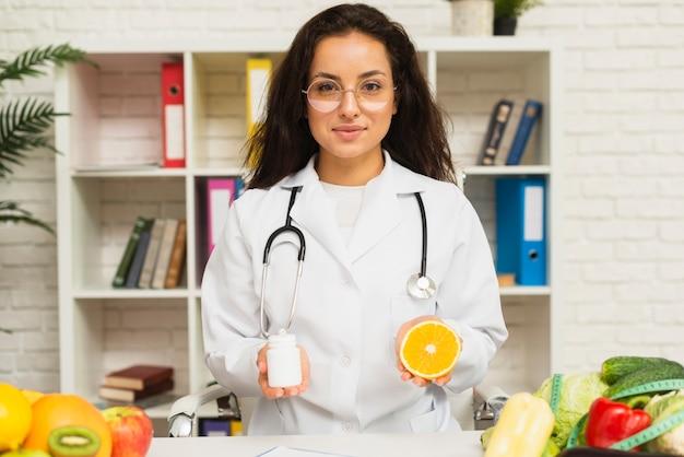 Middellange geschotene arts met stethoscoop en sinaasappel
