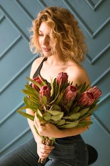 Middellange geschotene blondevrouw met bloemenboeket