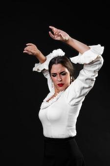 Middellange geschotene dame die flamencodans met omhoog wapens uitvoert