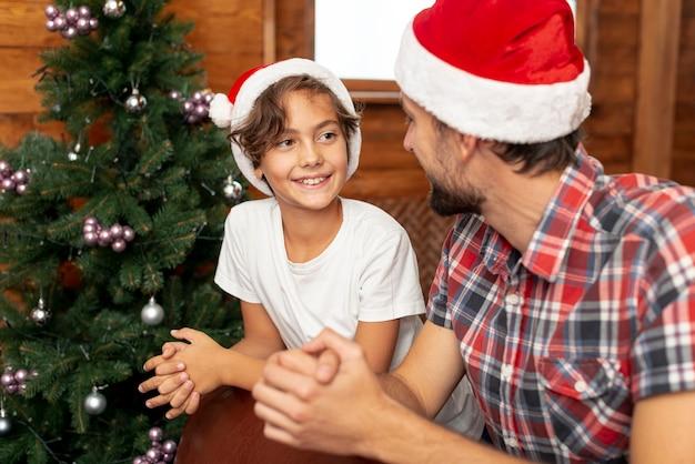 Middellange geschotene jongen met vaderzitting dichtbij kerstmisboom