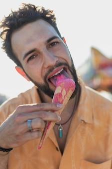 Middellange geschotene kerel die met bruin haar roomijs eet