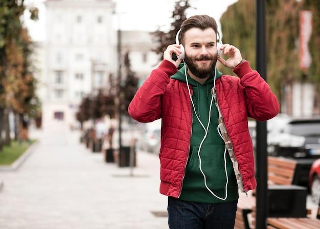 Middellange geschotene kerel die met hoofdtelefoons in de stad loopt