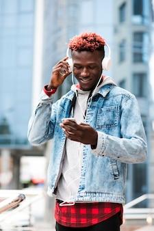 Middellange geschotene kerel die met hoofdtelefoons telefoon bekijkt
