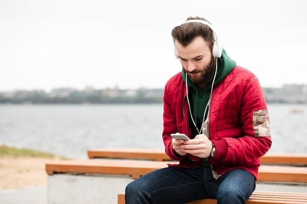 Middellange geschotene kerel die zijn smartphone bekijkt