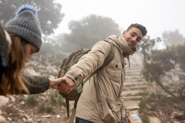 Middellange geschotene man die vrouw helpt te beklimmen