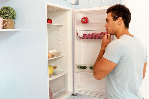 Middellange geschotene mens die in de koelkast kijkt
