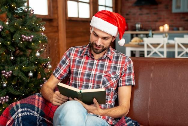 Middellange geschotene mens die met rode hoed een boek leest