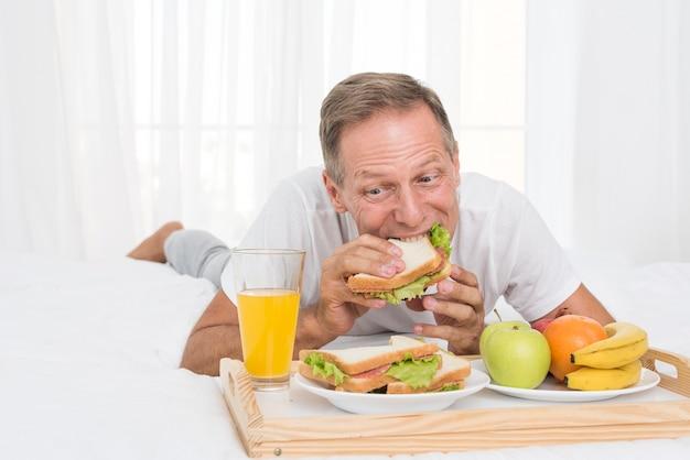 Middellange geschotene mens die ontbijt in bed heeft
