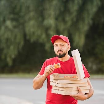 Middellange geschotene mens die pizza in openlucht eet