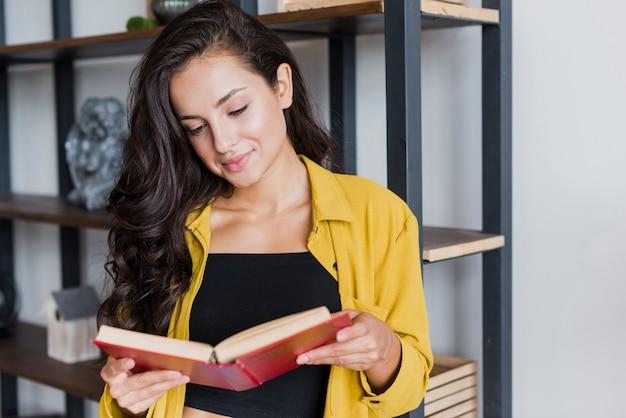 Middellange geschotene mooie vrouw die een boek leest