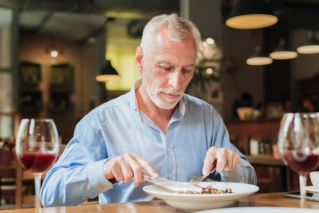 Middellange geschotene oude mens die bij restaurant eet