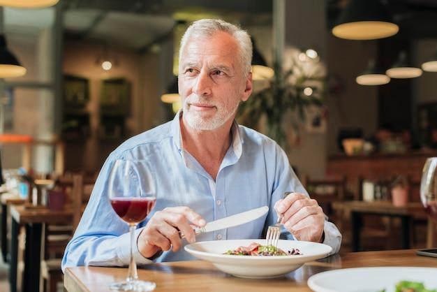 Middellange geschotene oude mens die een maaltijd hebben bij restaurant
