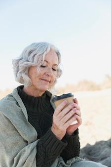 Middellange geschotene oude vrouw met koffie in openlucht