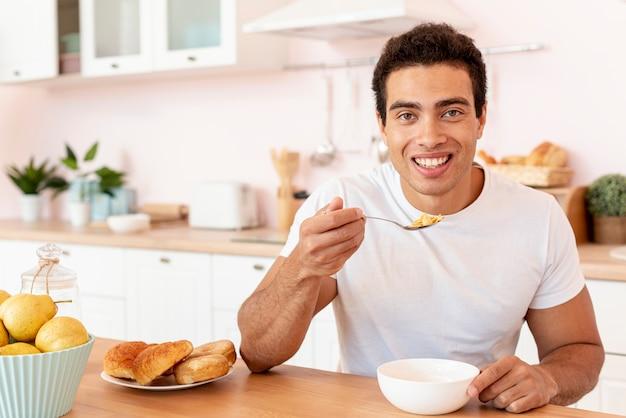 Middellange geschotene smileykerel die graangewassen eet