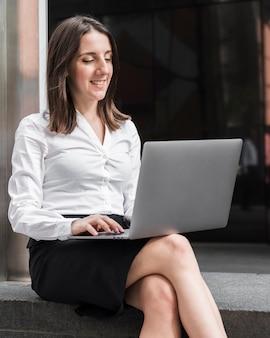 Middellange geschotene smileyvrouw die aan laptop werkt