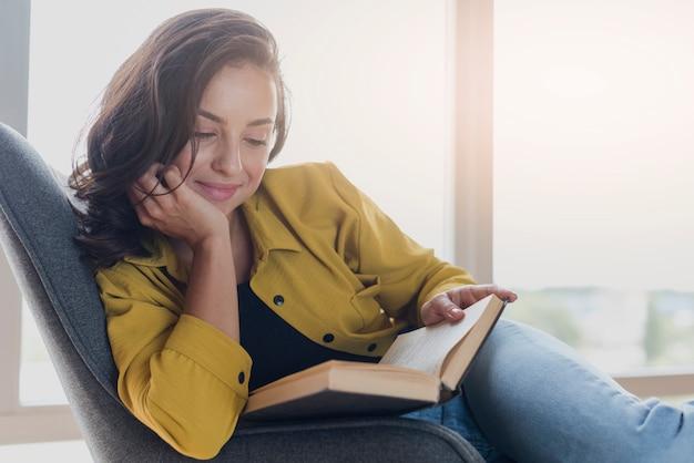 Middellange geschotene smileyvrouw met boek op stoel