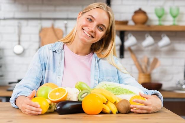 Middellange geschotene smileyvrouw met fruit in de keuken