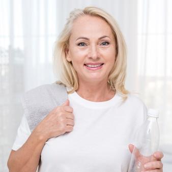Middellange geschotene smileyvrouw met handdoek en waterfles
