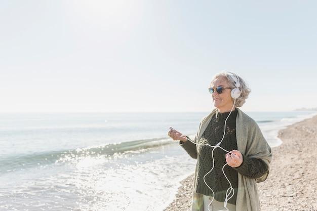 Middellange geschotene smileyvrouw met hoofdtelefoons in openlucht