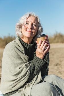 Middellange geschotene smileyvrouw met koffiekop