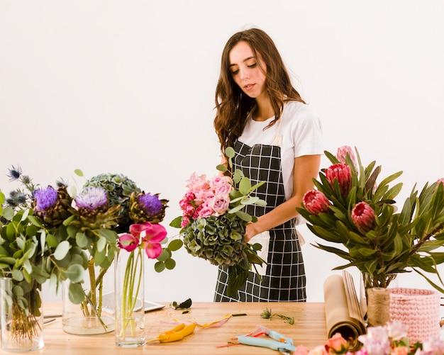 Middellange geschotene vrouw die bij een bloemenwinkel werkt