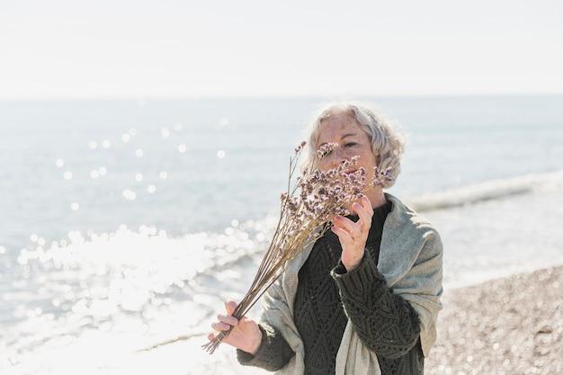 Middellange geschotene vrouw die bloemen bekijkt