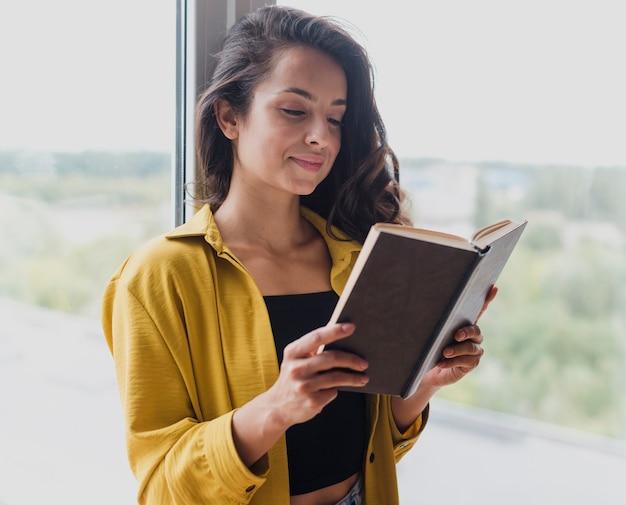 Middellange geschotene vrouw die een boek steunt