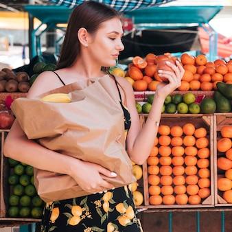 Middellange geschotene vrouw die een granaatappel bekijkt