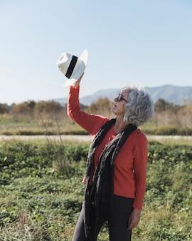 Middellange geschotene vrouw die een hoed steunt
