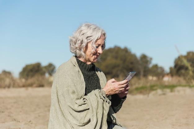 Middellange geschotene vrouw die haar telefoon bekijkt