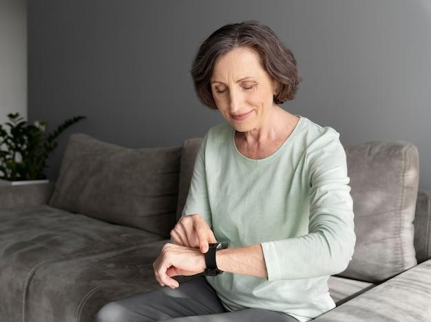 Middellange geschotene vrouw die horloge controleert