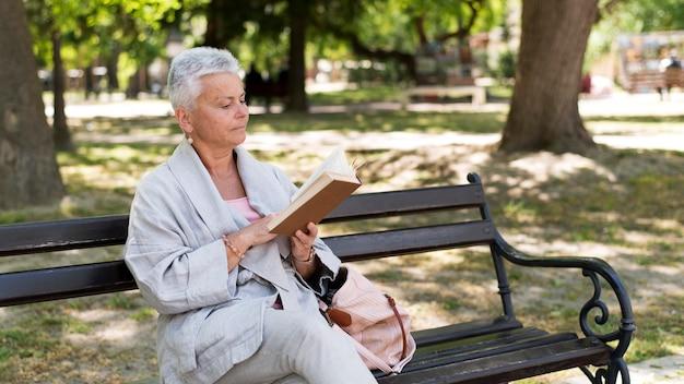 Middellange geschotene vrouw die in park leest