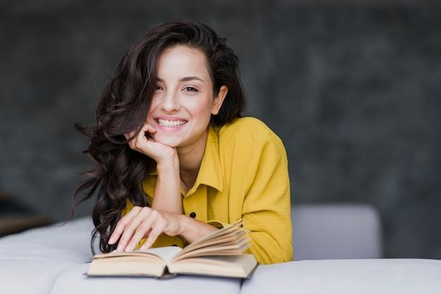 Middellange geschotene vrouw die met boek bij camera glimlachen